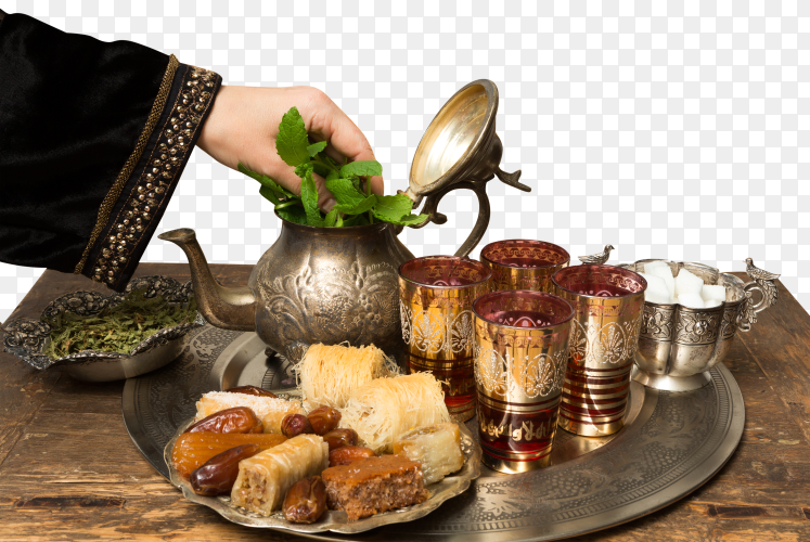 Female hand adding mint leaves to a tray with dates, cookies and tea the moroccan style on transparent background PNG